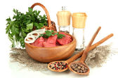 Raw beef meat in bowl with herbs and spices isolated on white — Stock Photo