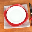 Empty red and white plates with fork and knife on wooden table, close-up — Stock Photo #16987763