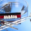 Denture with dental tools on blue background — Stok fotoğraf