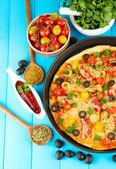 Colorful composition of delicious pizza, vegetables and spices on blue wooden background close-up — Stock Photo