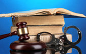 Gavel, handcuffs and book on law on blue background — Stock Photo