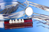Set of dental tools with denture on blue background — Stok fotoğraf