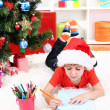 Stock Photo: Little boy in Santa hat writes letter to Santa Claus