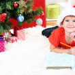 Little boy in Santa hat writes letter to Santa Claus - Stock Photo