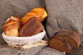 在关于解雇背景的木桌上的篮子里的新鲜面包 — 图库照片