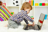 Cute little boy and notebook in room — Stockfoto