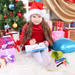 Stock Photo: Beautiful little girl in red dress writes letter to SantClaus in festively decorated room