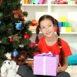 Little girl holding gift box near christmas tree — Stock Photo #17183235