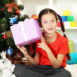 Little girl holding gift box near christmas tree — Stock Photo #17183273