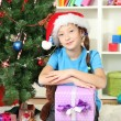 Little girl holding gift box near christmas tree — Stock Photo #17183279
