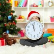 Little girl holding clock near christmas tree — Stock Photo