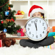 Little girl holding clock near christmas tree — Stock fotografie