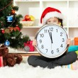 Little girl holding clock near christmas tree — Stok fotoğraf