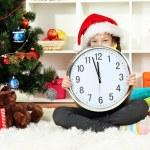 Little girl holding clock near christmas tree — Stock Photo #17183291