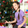Little girl decorating christmas tree — Stock Photo #17183293