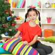 Little girl sitting near christmas tree — Stock Photo #17183307