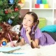 Little girl writing letter to Santa near christmas tree — Stok fotoğraf