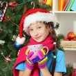 Little girl with pink scarf and cup of hot drink  sitting near christmas tree — Stok fotoğraf