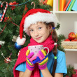 Little girl with pink scarf and cup of hot drink  sitting near christmas tree — Stockfoto