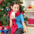 Little girl with pink scarf and glass of milk sitting near christmas tree — Stock fotografie