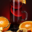 Fragrant mulled wine in glass with spices and oranges around on red background — Stock Photo #17183411