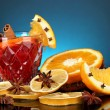 Fragrant mulled wine in glass with spices and oranges around on blue background - Stok fotoğraf