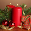 Two candles and christmas decorations, on brown background — Stock Photo #17183565