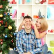 Young happy couple near a Christmas tree at home — Stock Photo #17183897