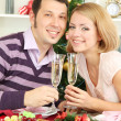 Young happy couple holding glasses with champagne at table near Christmas tree — Stock Photo