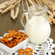 Tasty pretzels in white bowl and milk jug on wooden table close-up - Stock Photo