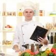 Chef thinking with book recipe in cuisine — Stock Photo