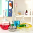 Different laboratory glassware with color liquid on laboratory background — Stock Photo