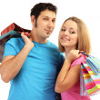 Young couple shopping and holding many shopping bags isolated on white — Stock Photo #17187815