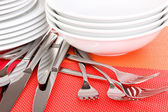 Forks, knifes and spoons on red mat close-up — Stock Photo