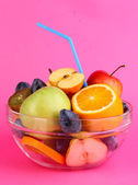 Glass bowl with fruit for diet on pink background — Stock Photo