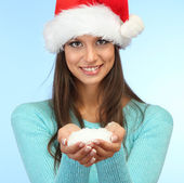 Beautiful young woman holding snow, on blue background — Stock Photo