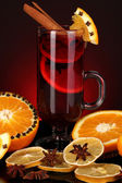 Fragrant mulled wine in glass with spices and oranges around on red background — Stock Photo