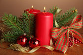 Two candles and christmas decorations, on brown background — Стоковое фото
