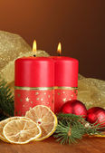 Two candles and christmas decorations, on wooden background — Stock Photo