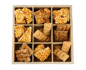 Tasty sweets (kozinaki)in wooden crate, isolated on white — Stock Photo