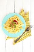 Plato de pasta rigatoni con salsa de tomate sobre tabla de madera blanca — Foto de Stock