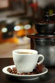 Cup of coffee, grinder, turk and coffee beans in cafe — Stock Photo