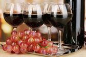 červené víno ve sklenici a láhev na pozadí místnosti — Stock fotografie