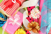 Rolls of Christmas wrapping paper with ribbons, bows on color background — Stock Photo