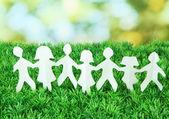 Papír na zelené trávě na světlé pozadí — Stock fotografie