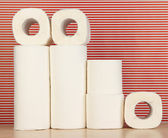 Rolls of toilet paper on striped red background — Zdjęcie stockowe