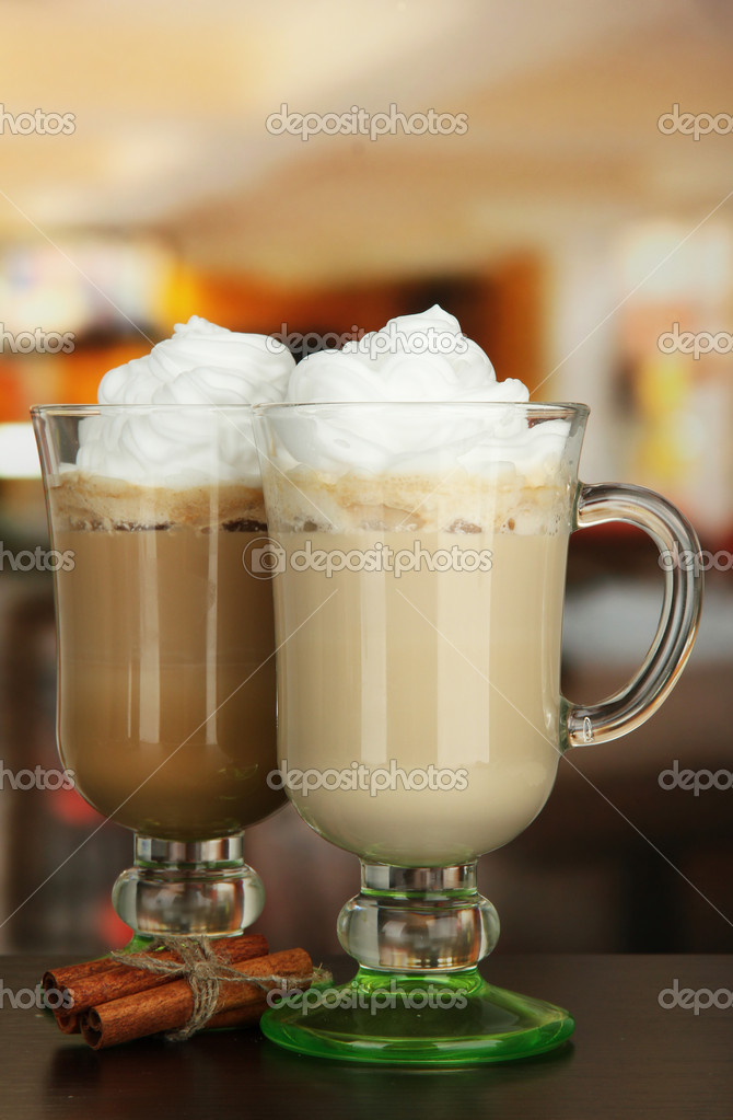 Fragrant coffee latte in glasses cups with vanilla pods, on table in cafe — Stock Photo #17187749