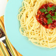 Italian spaghetti in plate on wooden table — Stock Photo