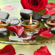 Spa stones with rose petals and candles in water on plate — Stock Photo