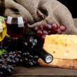 Bottles and glasses of wine, cheese and grapes on grey background — Stock Photo #17213163